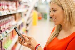 Mulher no supermercado que verifica preços de seu smartphone Fotografia de Stock Royalty Free