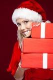 A mulher no tampão do Natal prende um jogo dos presentes fotografia de stock royalty free