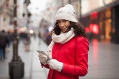Mulher no tampão vermelho do revestimento e das lãs e luvas com o smartphone em han Imagem de Stock Royalty Free