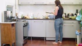 A mulher no tanque preto das calças de brim e com fones de ouvido cozinha panquecas na cozinha video estoque