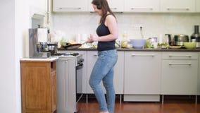 A mulher no tanque preto das calças de brim e com fones de ouvido cozinha panquecas na cozinha filme