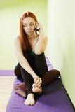 Mulher no telefone celular no gym Fotografia de Stock Royalty Free