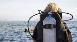 Mulher no terno de mergulho com o escafandro pronto para mergulhar no mar fotos de stock