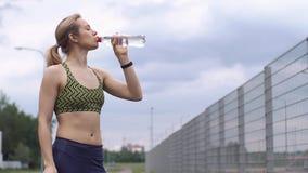 A mulher no terno movimentando-se bebe a água filme