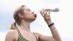A mulher no terno movimentando-se bebe a água video estoque