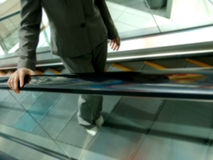 Mulher no terno que vai acima a escada rolante Foto de Stock Royalty Free