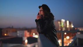 A mulher no terracce olha para a frente e aprecia a calma da cidade da noite video estoque