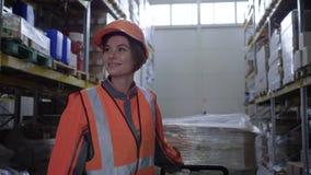 Mulher no trabalho duro, trabalhador no uniforme que puxa o trole com as caixas entre fileiras das cremalheiras no armazém video estoque