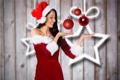 Mulher no traje de Santa que gesticula contra o fundo digitalmente gerado Imagem de Stock Royalty Free