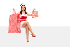 Mulher no traje de Santa que guarda sacos de compras Imagem de Stock