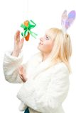 A mulher no traje do coelho estica para fora para a cenoura Imagens de Stock Royalty Free