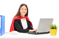 Mulher no traje do super-herói que trabalha no portátil Fotografia de Stock Royalty Free
