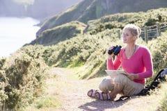 Mulher no trajeto do cliffside usando binóculos fotografia de stock royalty free