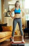 Mulher no treinamento moderno da casa usando a placa do poder da vibra??o imagens de stock royalty free