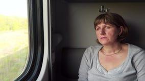 A mulher no trem olha para fora a janela vídeos de arquivo