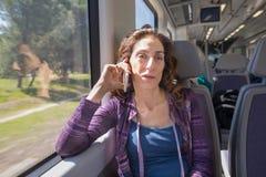 Mulher no trem que fala no móbil imagem de stock royalty free