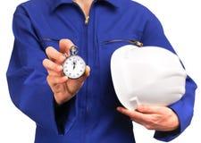 Mulher no uniforme azul do trabalho que guarda um cronômetro Foto de Stock