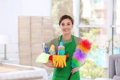 Mulher no uniforme com fontes de limpeza imagem de stock royalty free