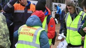 A mulher no uniforme do salvamento distribui camisas aos salvadores novos na rua ensino vídeos de arquivo