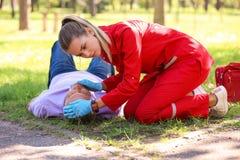 Mulher no uniforme que verifica para ver se há respirar do homem inconsciente fora imagem de stock royalty free