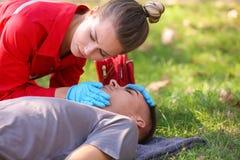 Mulher no uniforme que verifica para ver se há respirar do homem inconsciente fora foto de stock royalty free