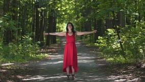 A mulher no vermelho aprecia a natureza, sente a unidade com espírito divinos da floresta, bênção vídeos de arquivo