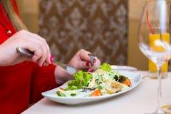 A mulher no vermelho come a salada natural Comer e dieta saudáveis foto de stock royalty free