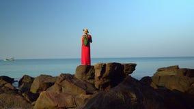 A mulher no vermelho em um vestido com uma trouxa custa o endireitamento das mãos em pedras pretas grandes na costa do vídeos de arquivo