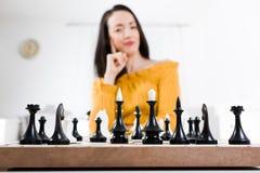 Mulher no vestido amarelo que senta-se na frente da xadrez - estratégia foto de stock royalty free