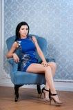 Mulher no vestido azul curto que senta-se na cadeira imagens de stock royalty free