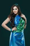 A mulher no vestido azul esverdeado brilhante com penas do pavão projeta Composição criativa da fantasia, cabelo escuro longo Foto de Stock Royalty Free