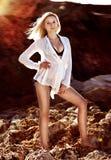 Mulher no vestido branco e no biquini que estão na praia fotografia de stock
