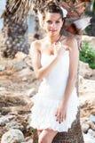 Mulher no vestido branco na praia tropical perto das palmeiras Foto de Stock