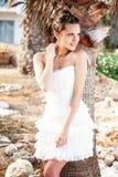 Mulher no vestido branco na praia tropical perto das palmeiras Foto de Stock Royalty Free