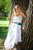 Mulher no vestido branco no parque verde que senta-se na árvore Conceito verde de Eco Fotografia de Stock