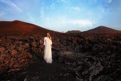 Mulher no vestido branco que está no monte breathink com olhos fechados Lanzarote, Ilhas Canárias, Spain Imagem de Stock
