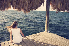 Mulher no vestido branco que olha o oceano Foto de Stock Royalty Free