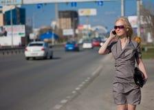 Mulher no vestido cinzento que anda e que chama pelo telefone Fotografia de Stock Royalty Free