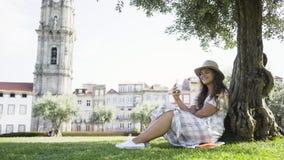 Mulher no vestido com o smartphone que senta-se sob a árvore no parque filme