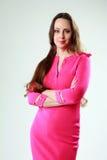 A mulher no vestido cor-de-rosa com braços dobrou a posição Foto de Stock