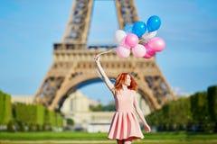 Mulher no vestido cor-de-rosa com grupo dos balões que dançam perto da torre Eiffel em Paris, França Imagem de Stock Royalty Free