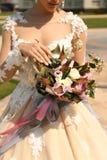 Mulher no vestido de casamento elegante que guarda o bouque luxuoso do casamento foto de stock royalty free