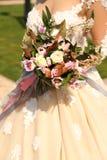 Mulher no vestido de casamento elegante que guarda o bouque luxuoso do casamento foto de stock