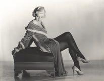 Mulher no vestido de veludo que senta-se no banquinho imagens de stock royalty free