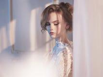 Mulher no vestido do laço na janela imagem de stock royalty free