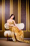 Mulher no vestido do ouro Fotografia de Stock Royalty Free