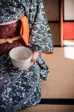 Mulher no vestido do quimono que guarda o copo de chá japonês, Japão foto de stock