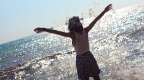 Mulher no vestido do verão que está em uma costa de mar e que olha ao horizonte Fotografia de Stock Royalty Free
