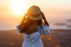 A mulher no vestido e com chapéu é olhares no por do sol fotos de stock royalty free
