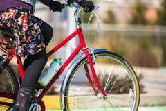 A mulher no vestido e nas botas faz a senhoras o passeio da bicicleta imagens de stock royalty free